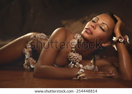 Beautiful woman in shells accessories lying on the beach - stock photo