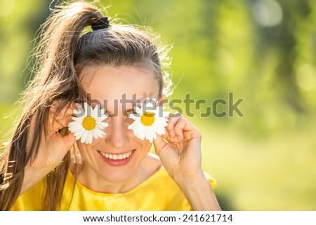 Beautiful woman in spring garden with flowers on her eyes. Summer fun concept. soft daylight - stock photo