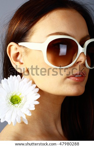 Beautiful woman in sunglasses with flower in her hair. isolated on gray - stock photo