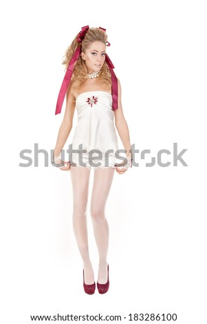 Beautiful woman in the doll style with red bow and red shoes isolated on a white background. - stock photo