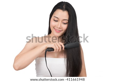 Beautiful woman is doing her hair with straightener  - stock photo