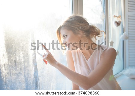 beautiful woman with fresh daily makeup and romantic wavy hairstyle, sitting at the windowsill, draws on glass