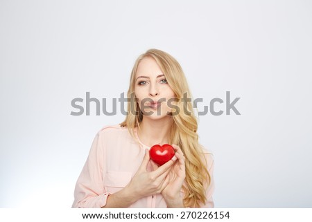 Beautiful young blond hair woman holding heart shaped valentine stone and smiling while standing isolated on white