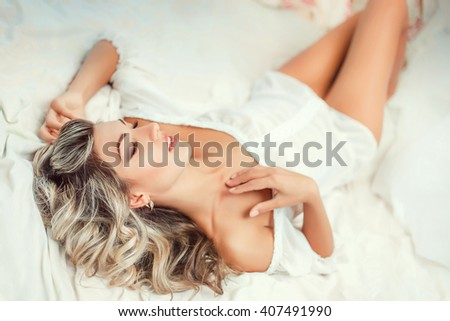 beautiful young blond woman in white body basking in the morning in bed,fashionable toning creative computer colors