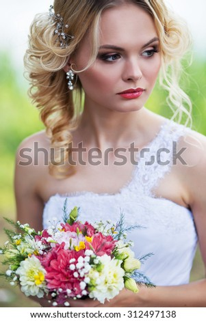 beautiful young bride posing in the summer forest