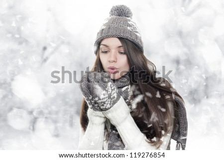 Beautiful young brunette woman heating hands on winter background - stock photo