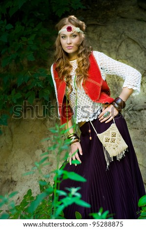 Beautiful young girl hippie posing in a wood - stock photo