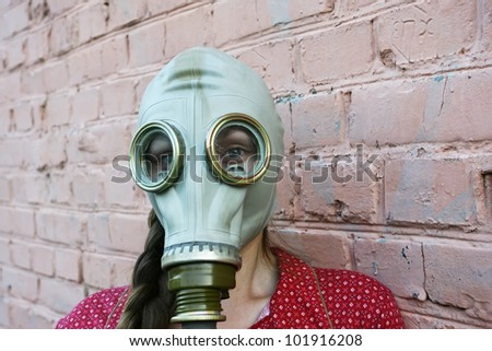 beautiful young girl in a gas mask - stock photo