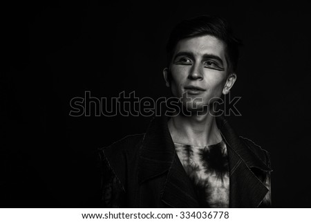 Beautiful young man with beautiful makeup on a dark background.  Portrait of a young boy in the original image. Styolnyy clothing and accessories. Photo for fashion magazines, posters and websites.