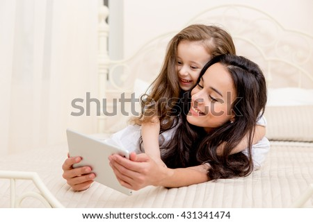 beautiful young mother and her cute daughter in white shirts and jeans lying on the bed at home , laughing and looking in digital tablet