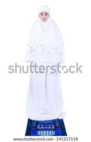 Beautiful young muslim woman praying - isolated on white  - stock photo