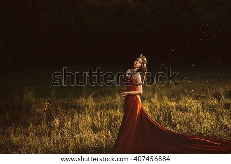 Beautiful young princess in a long red dress walks among the green plants in the woods , a fashionable toning , creative color