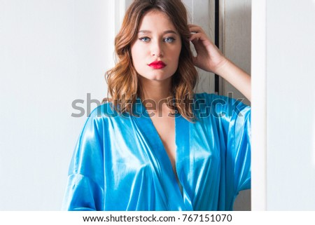 Beautiful young sexy girl in blue mantle posing on the bedroom door, erotic, seductive, boudoir concept