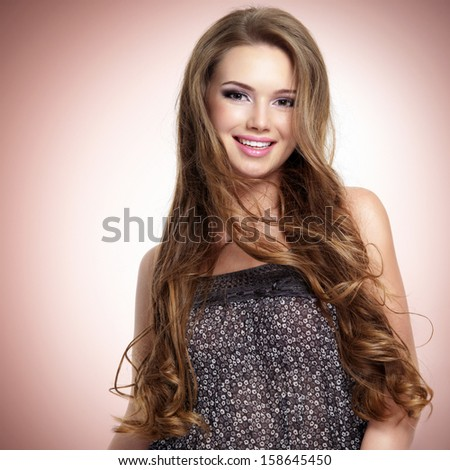 Beautiful  young smiling woman with long hairs looking at camera. Studio portrait. - stock photo
