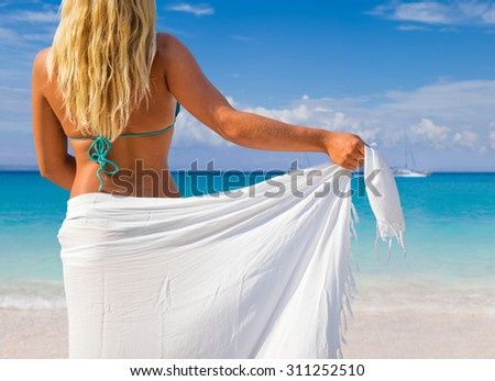 Beautiful young woman in white sarong on the beach. - stock photo