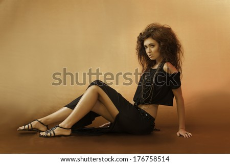 Beautiful young woman sitting down in a sexy black outfit with wild hair and gladiator sandals looking over her shoulder - stock photo