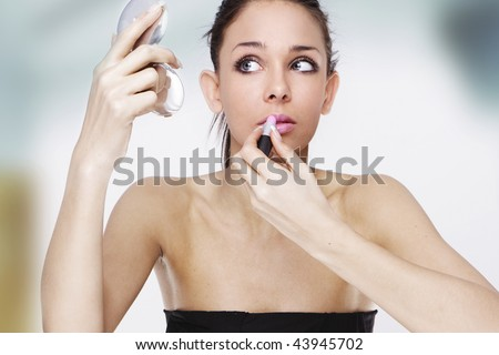 Beautiful young woman stressed before her date looking at the mirror applying makeup - stock photo