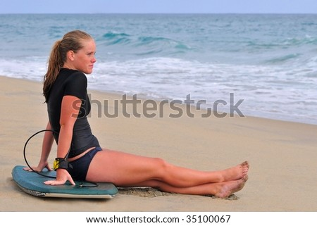 Beautiful young woman watches waves with bodyboard on beach