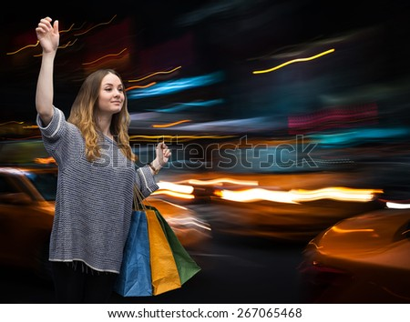 Beautiful young woman with shopping bags during sales season in the big city - stock photo