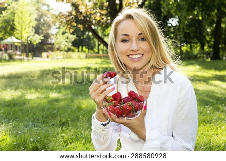 beautiful young woman with strawberries on the grass