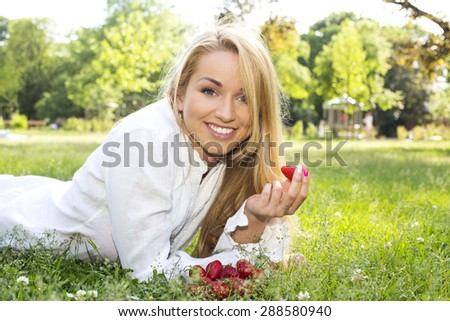 beautiful young woman with strawberries on the grass - stock photo