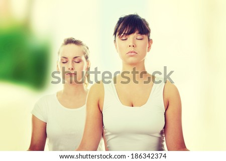 2 Beautiful young womans doing yoga exercise - stock photo