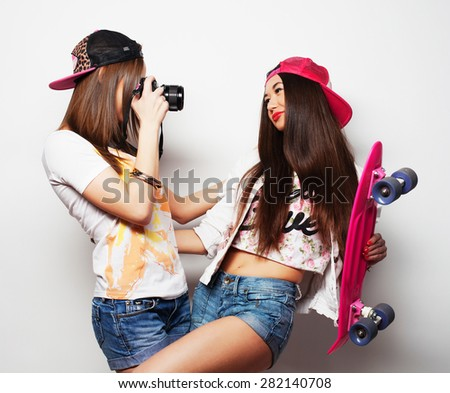 Beautiful young women in summer clothes holding pink skateboard and take picture while standing against grey background  - stock photo