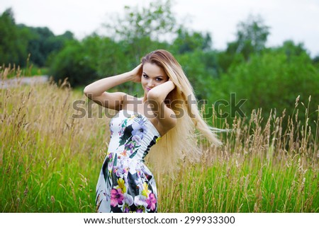 Beauty Girl Outdoors enjoying nature, blond girl in dress  on a meadow - stock photo
