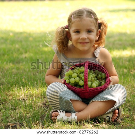 beauty little girl sitting and holding basket with grape