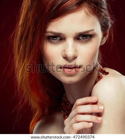beauty portrait of a young woman looking into the camera in a beautiful red necklace