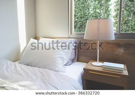 bedroom interior design with pillows on bed and decorative table lamp. - stock photo