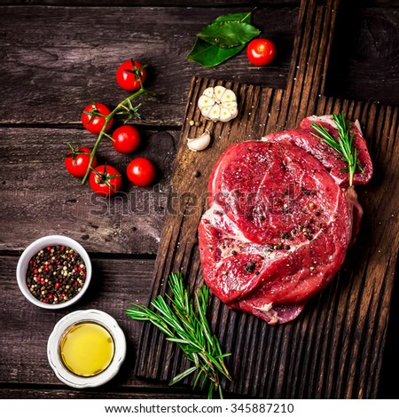 Beef on a chopping board, tomatoes,herbs and spices on dark wooden table. Style rustic, selective focus. - stock photo
