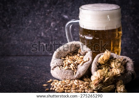 beer,barley and hops on stone table - stock photo