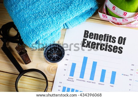 """""""Benefits of Exercise"""" text on paper with blue bar chart on wooden table with compass,magnifying glass, pen, towel, green apple with measurement tape, and whistles - fitness, diet and healthy concept - stock photo"""