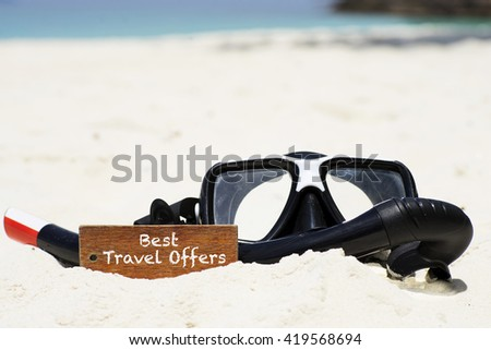 """Best Travel Offers"" text on wooden keychain withs scuba diving mask and snorkel on the tropical white sand beach - vacation and business concept - stock photo"