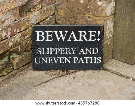 """Beware! Slippery and Uneven Paths"" Sign in a Country Cottage Garden in the Rural Village of Tintinhull in Somerset, England,UK"