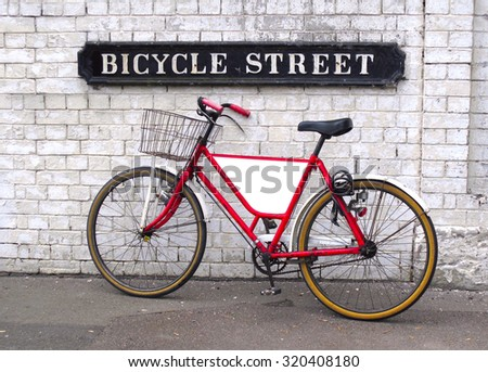 Bicycle Street sign with a bicycle leaning against a wall with an empty panel for your logo or message                            - stock photo
