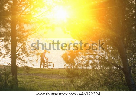 Bicyclists on walk in summer forest near the river in the sunlight - stock photo
