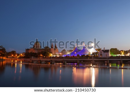 """Big Top"" circus style blue tent and Galway Cathedral on the bank of Corrib river in Galway, Ireland - stock photo"