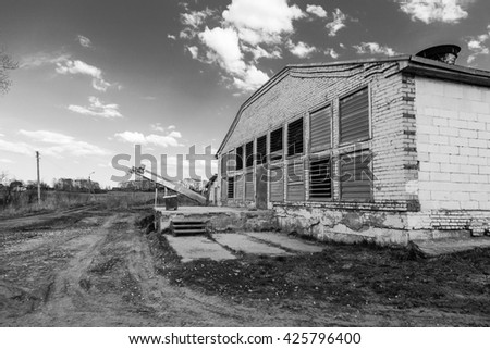 big white Poultry Farm henhouse in a cloudy day dirty road - stock photo