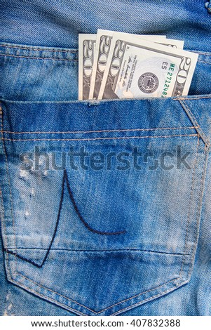 $ 20 bill in the pocket of jeans, jeans neatly stacked on wooden background, top view - stock photo