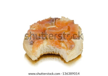 Bitten smoked salmon  on a piece of bread on white background.