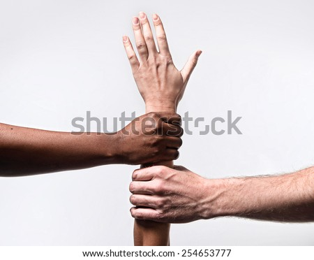 black African American and Caucasian hands holding together white skin arm in world unity and racial love , understanding in tolerance races diversity cooperation concept isolated on white background