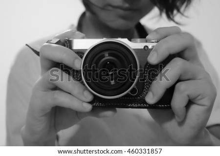Black and white. A woman is taking selfie in a mirror by a camera