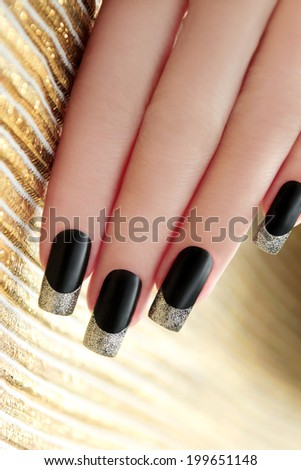 Black French manicure with Golden shining varnish on striped background  - stock photo
