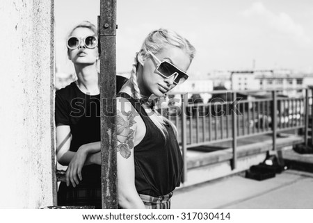 Black white portrait of two pretty blonde girls wearing plaid skirt and  black T-shirt. Girls smile, have fun against  urban city. - stock photo