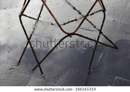 black wrought iron chair sitting on a patio casts a shadow. - stock photo