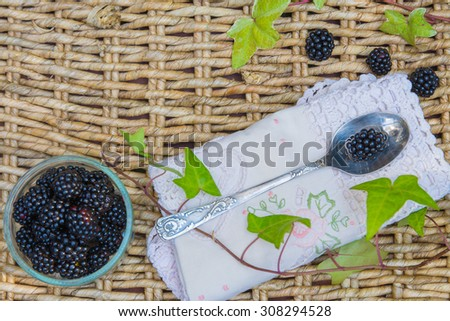 Blackberries in bowls on wicker background and vintage spoon, top view.   - stock photo
