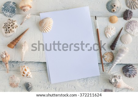 Blank artist sketchbook on white wooden background with seashells around it. View from the top. Open blank sketchbook. Artistic mockup template for your design.
