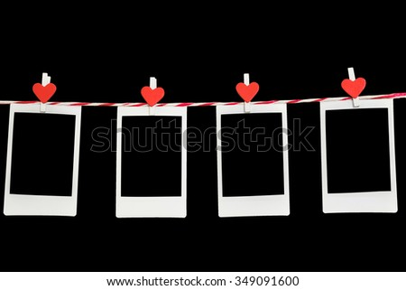 4 Blank instant photo and red clip paper heart hanging on the clothesline with black background.Designer concept. - stock photo